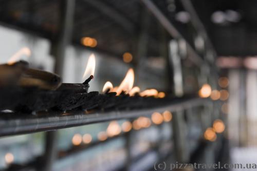 Посетители ставят свечки около Храма Зуба Будды.
